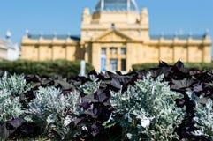 艺术亭子 一个老19世纪大厦在背景a中和植物在前面关闭  免版税库存图片