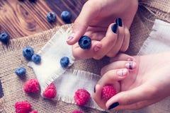 艺术修指甲和莓果 免版税库存照片