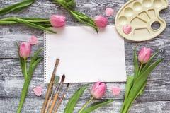 艺术册页、油漆刷、调色板和桃红色郁金香在灰色木 免版税库存照片
