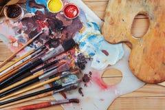 艺术刷子和色的墨水在罐头在黑暗的背景 免版税库存图片