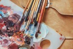 艺术刷子和色的墨水在罐头在黑暗的背景 库存图片