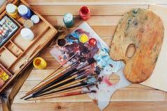 艺术刷子和色的墨水在罐头在黑暗的背景 免版税图库摄影