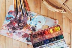 艺术刷子和色的墨水在罐头在黑暗的背景 免版税库存照片