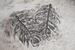 艺术和叶子印刷品在水泥地板上在庭院显示显示 免版税库存图片