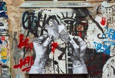 艺术品用在墙壁,未知的艺术家街道画上的手 免版税库存图片