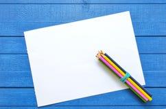 艺术品的在蓝色木背景的嘲笑图画的和文本与在空的板料的角落的四支色的铅笔 库存照片
