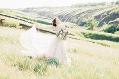 艺术婚礼摄影 有花束的美丽的有火车的新娘和礼服本质上 免版税库存照片