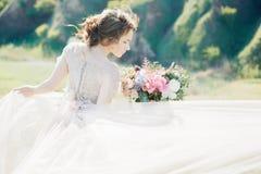 艺术婚礼摄影 有花束的美丽的有火车的新娘和礼服本质上 免版税库存图片