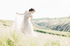 艺术婚礼摄影 有花束的美丽的有火车的新娘和礼服本质上 免版税图库摄影