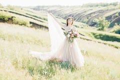 艺术婚礼摄影 有花束的美丽的有火车的新娘和礼服本质上 图库摄影