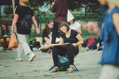 艺术学校油漆的女孩在露天的城市公园以纪念城市` s天 图库摄影