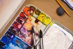 艺术家、一个调色板有水彩油漆的,刷子和帆布的创造性的过程的细节与剪影 免版税库存图片