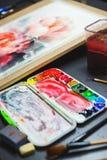 艺术家、一个调色板有水彩油漆的,刷子和帆布的创造性的过程的细节与剪影 库存照片