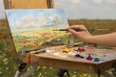艺术家与刷子的手油漆在自然 免版税库存照片