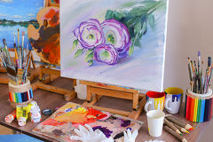 艺术家和立场绘的照片画在画架在艺术螺柱 图库摄影