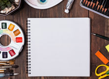 艺术家嘲笑与刷子、pensils和白纸 库存照片