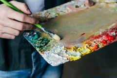 艺术家在帆布拿着有油漆和刷子的一个调色板和绘 混合油漆 免版税库存照片
