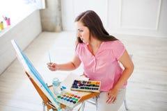 艺术家在帆布whith水彩的绘画图片 免版税库存照片
