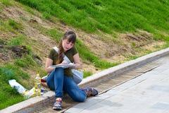 年轻艺术家在河的大学堤防工作 免版税库存图片
