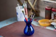 艺术家在蓝色花瓶的画笔 库存图片