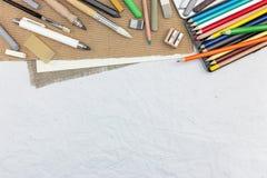 艺术家在被回收的纸背景的绘图工具 免版税库存图片