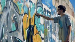 艺术家增加一些油漆到一张完成的街道画 股票录像
