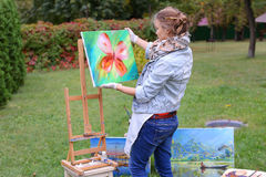 艺术家妇女拿着绘画并且看它,摆在的照相机 图库摄影