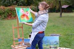 艺术家妇女拿着绘画并且看它,摆在的照相机 库存照片