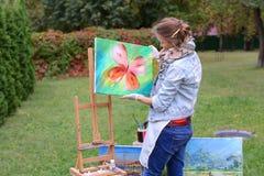艺术家妇女拿着绘画并且看它,摆在的照相机 免版税库存照片