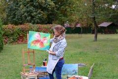 艺术家妇女拿着绘画并且看它,摆在的照相机 库存图片
