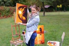 艺术家妇女拿着绘画并且看它,摆在的照相机 免版税图库摄影