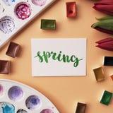 艺术家工作区 措辞在书法样式写的春天,红色郁金香,水彩,在桃子背景的调色板 平的位置 免版税库存照片