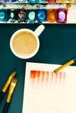艺术家工作地点 在水彩绘画教训的咖啡休息  纸、调色板、丙烯酸酯的油漆刷和一杯咖啡 的treadled 免版税库存图片