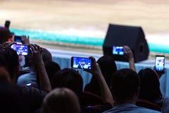 艺术家新年表现阶段的 许多观众在大厅拍摄他们的电话的音乐会节目 模糊的 图库摄影