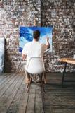 艺术家是油漆每油漆在艺术演播室,当坐在帆布前面时的一把椅子 画家在顶楼工作的图画过程 库存图片