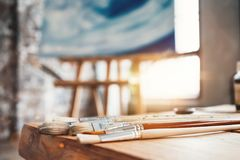艺术家特写镜头的油漆刷在一张木桌上的在演播室 在画架的背景帆布 画家车间 火光作用 免版税图库摄影