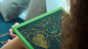 艺术家的年轻手,小孩艺术家绘与石墨铅笔的一块帆布,表和凹道坐帆布 影视素材