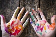 艺术家的手被弄脏的色的水彩油漆的在背景木 图库摄影
