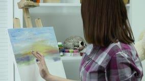 艺术家绘帆布的一名妇女并且抹上一把宽广的刷子 帆布在画架站立 艺术家画在画架 影视素材