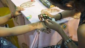 艺术家绘画在儿童手上的无刺指甲花纹身花刺 免版税图库摄影