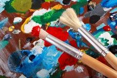 艺术家调色板和两把油漆刷 免版税库存图片