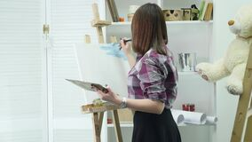 艺术家走向图片并且开始对油漆在一个明亮的演播室上油 创造性的男性艺术家图画图片与 股票视频