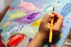 艺术家递与绘画的油漆刷 免版税库存照片