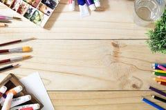 艺术家颜色铅笔和纸书桌在木桌上 免版税图库摄影