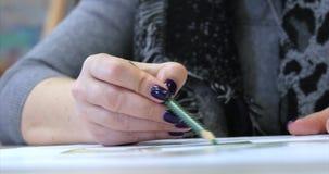 艺术家,妇女艺术家的年轻手绘与石墨铅笔的一块帆布,桌和凹道坐帆布 股票视频