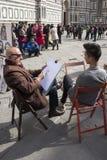 艺术家画一个年轻人 参观Giotto的钟楼的游人 免版税库存照片