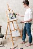 艺术家画在画架的一幅美丽的图画 免版税库存照片