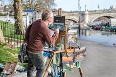 艺术家绘画河风景 免版税库存照片