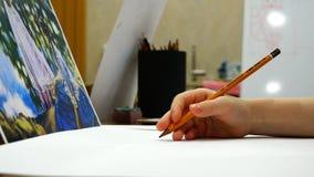 年轻艺术家` s手拿着在一张白色纸片的一支铅笔 影视素材
