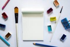 艺术工具和空白的笔记薄在白色桌上 绘画艺术供应-刷子,水彩,铅笔 库存照片